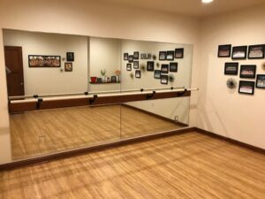 ballet room with mirrored wall and bar